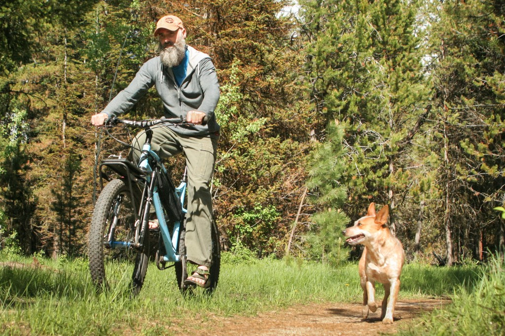 Aaron cycling with the coolest companion in the West, beloved dog Daisy.