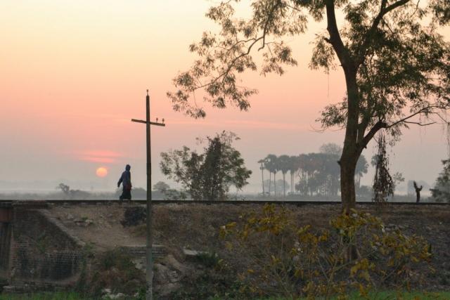 man walking on railway at sunrise