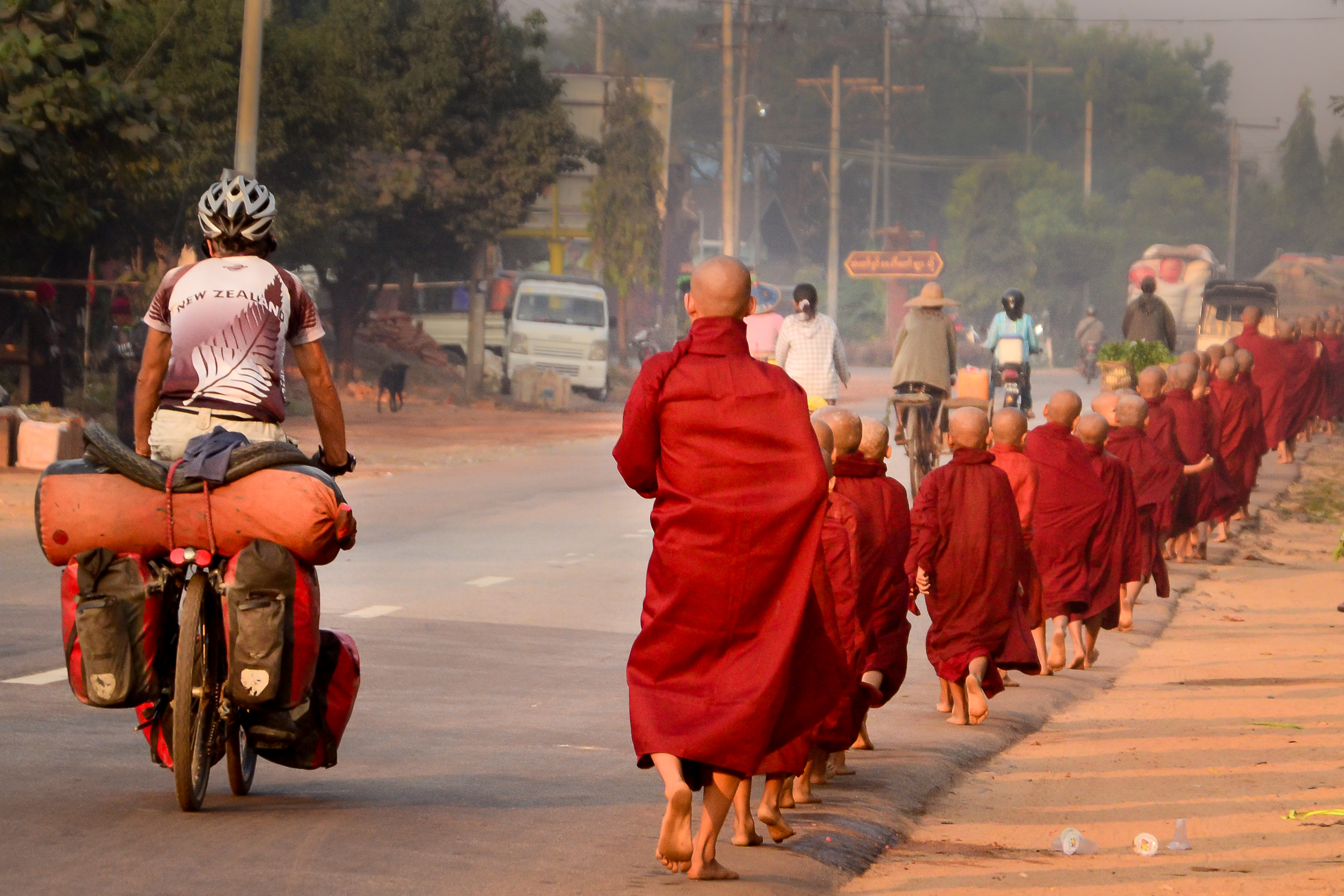 monks and cyclist in Myanmar