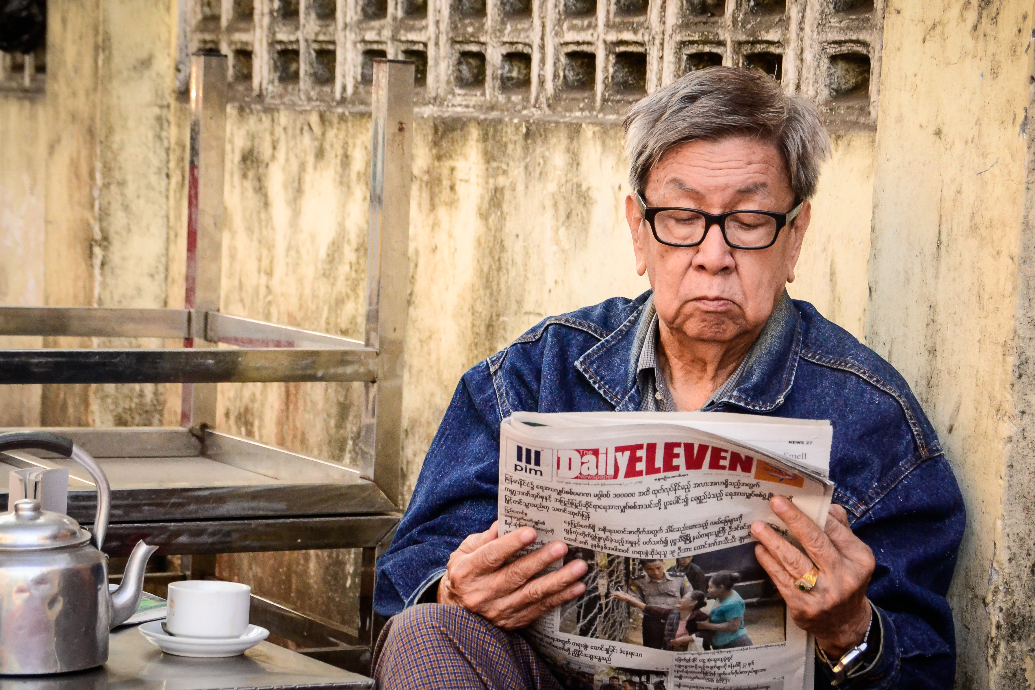 man reading newspaper in Myanmar
